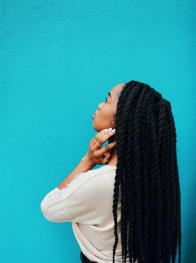 woman with long locs in front of blue wall - set your freelancer rate