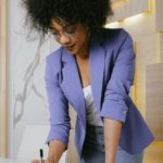 young black woman in purple blazer working- how to start freelancing