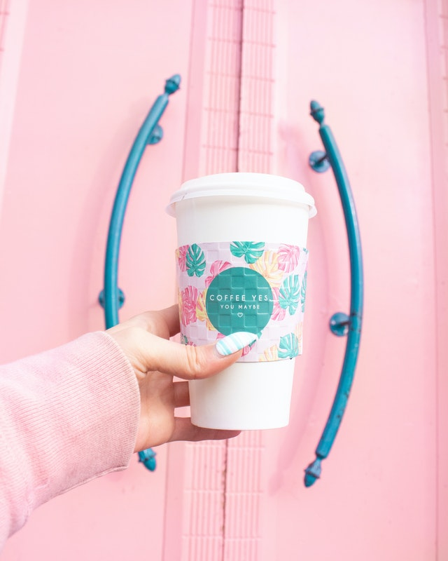 woman holding disposable coffee cup with pink background