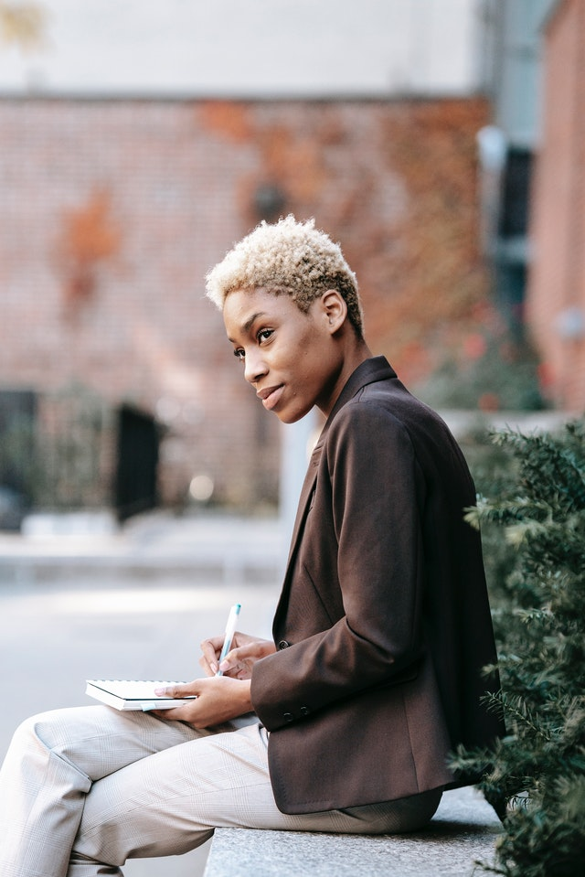 woman sitting outside with laptop for article on launching a freelance bookkeeping service
