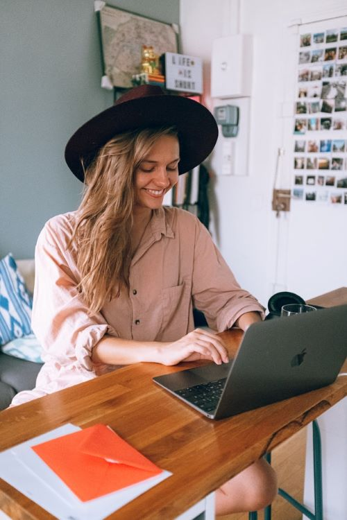 smiling woman wearing hat at table with laptop-daria-shevtsova-3277920