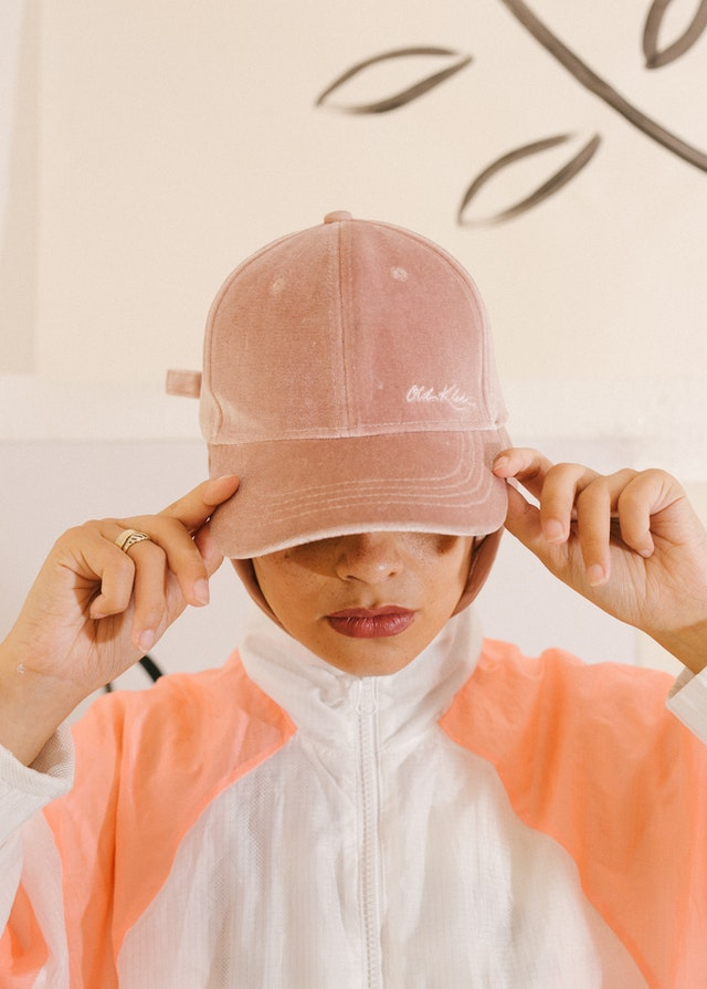 woman with face tilted down in pink baseball cap - mystery shopper