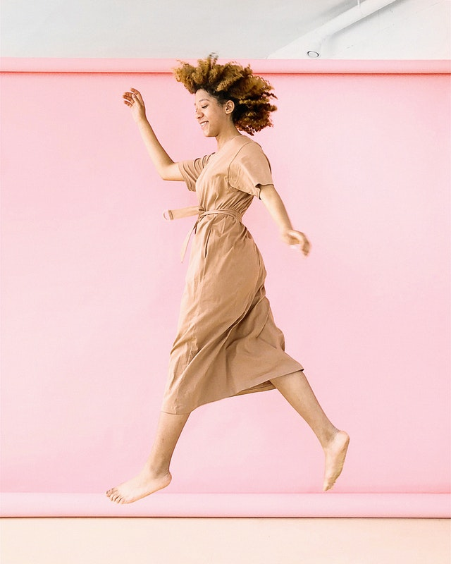 woman walking in a dress against pink background