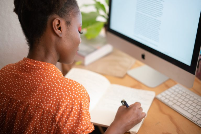 woman in orange shirt writing notes by hand - upwork tips